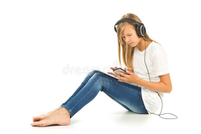 Junges Mädchen, das auf dem Boden mit Tabletten-PC, -Smartphone und -h sitzt lizenzfreie stockfotografie