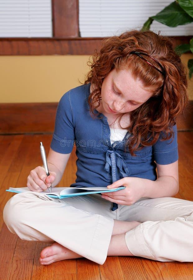 Junges Mädchen, das auf dem Fußbodenschreiben sitzt stockfoto