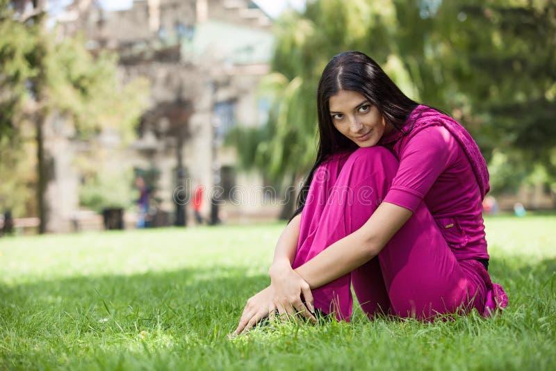 Junges Mädchen, das auf dem Gras im Park sitzt lizenzfreie stockfotos