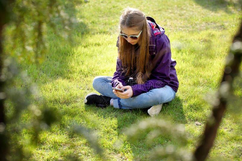 Junges Mädchen, das auf dem Gras mit Handy sitzt lizenzfreie stockfotografie