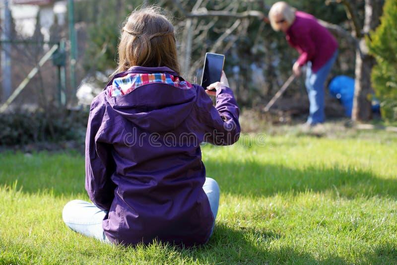 Junges Mädchen, das auf dem Gras sitzt und Foto am Arbeitsw tut lizenzfreies stockfoto