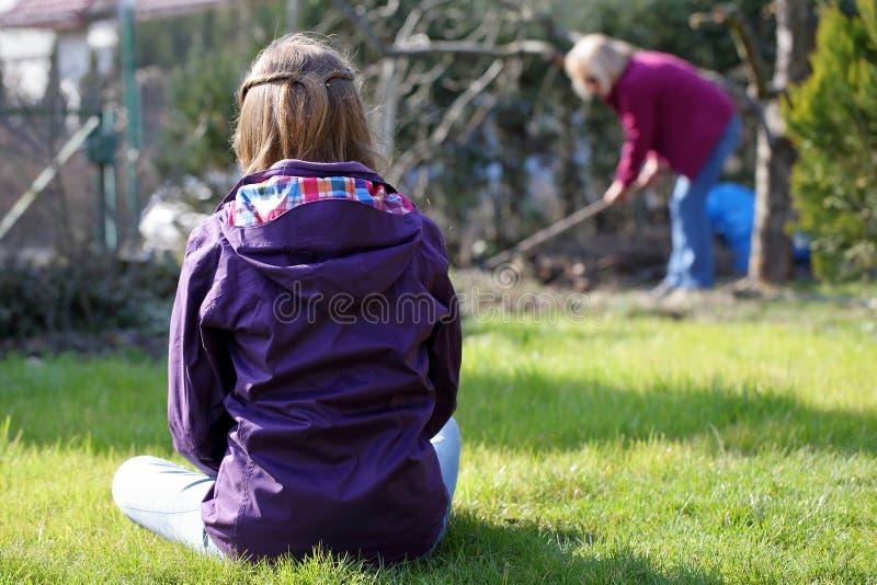 Junges Mädchen, das auf dem Gras und den Blicken an der berufstätigen Frau sitzt lizenzfreie stockfotografie