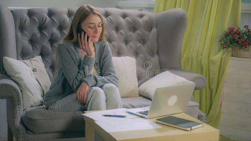 Junges Mädchen, das auf dem Smartphone, Anmerkungen auf Diagrammen und Laptop machend spricht stockfoto