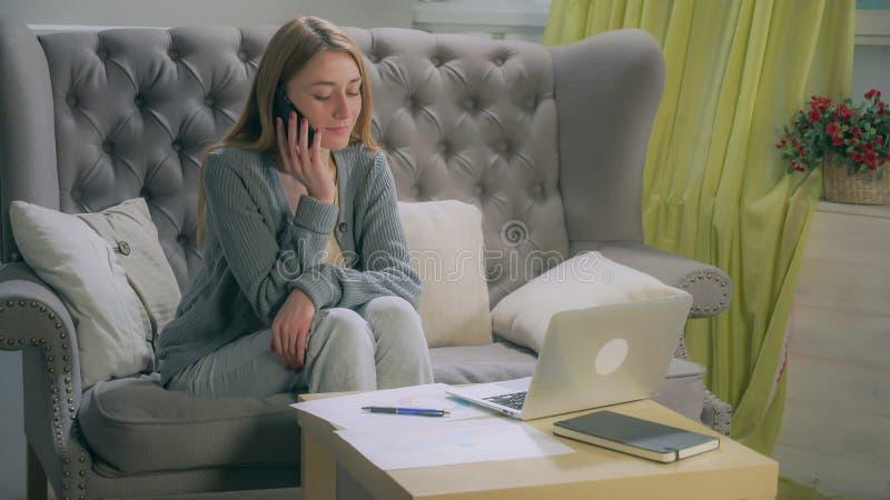 Junges Mädchen, das auf dem Smartphone, Anmerkungen auf Diagrammen und Laptop machend spricht lizenzfreie stockbilder