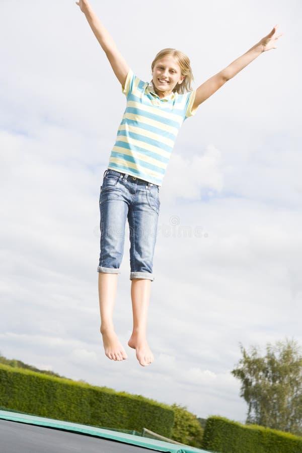 Junges Mädchen, das auf dem Trampolinelächeln springt stockfotos
