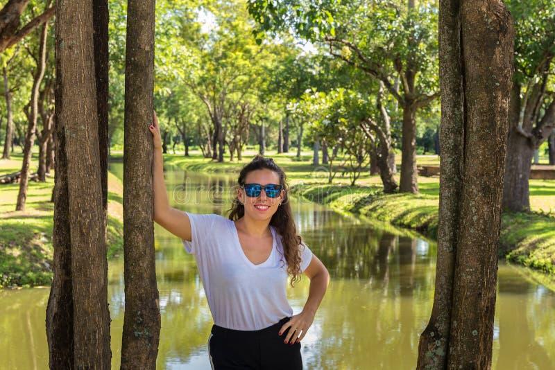 Junges Mädchen, das auf dem Ufer von einem Fluss aufwirft stockfotos