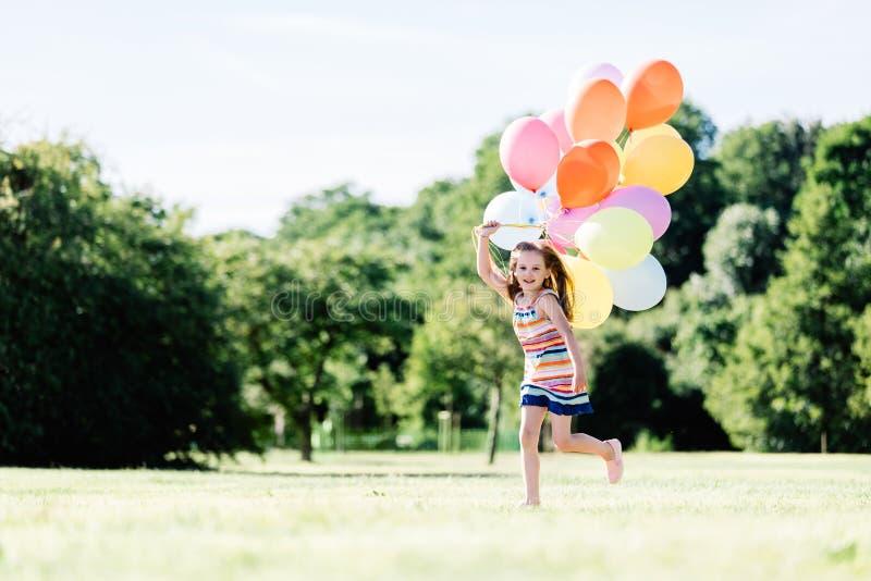 Junges Mädchen, das auf der Rasenfläche mit Ballonen läuft stockbild