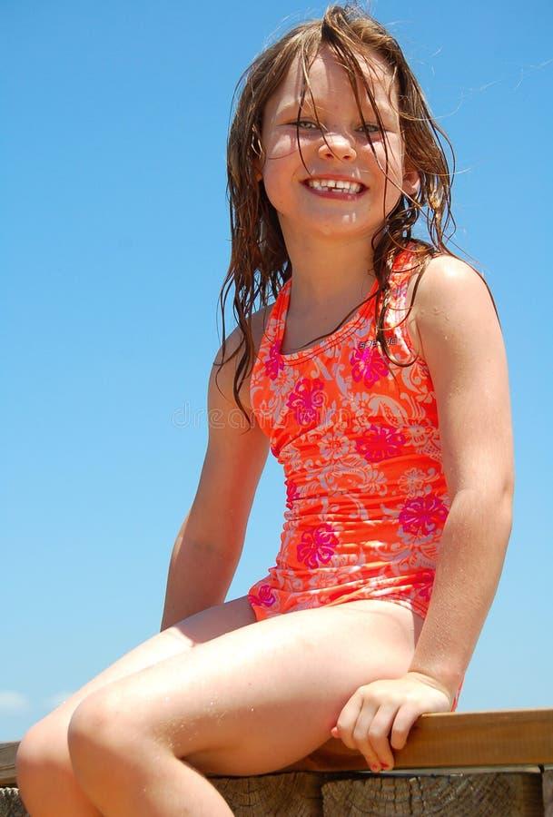 Junges Mädchen, das auf Dock sitzt stockfotos