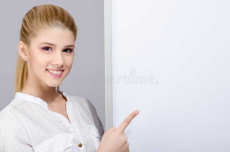 Junges Mädchen, das auf ein weißes leeres Brett lächelt und zeigt. stockbilder