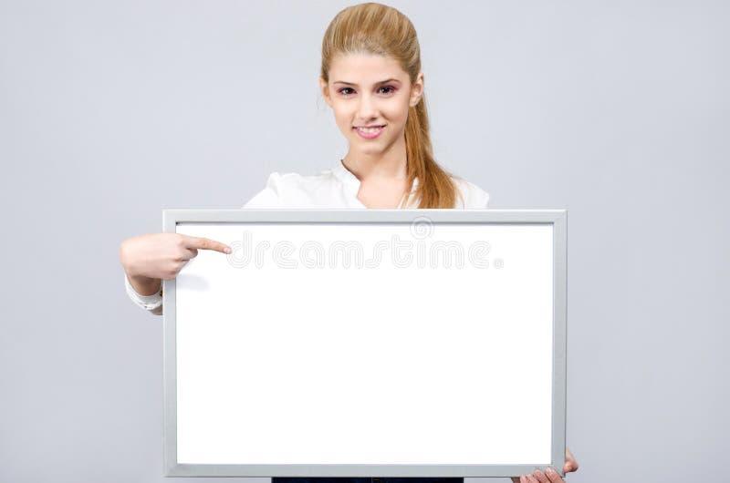 Junges Mädchen, das auf ein weißes leeres Brett lächelt und zeigt. lizenzfreie stockbilder
