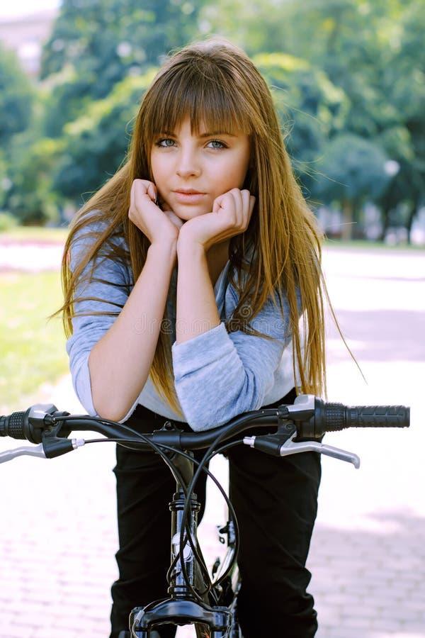 Junges Mädchen, das auf einem Fahrrad aufwirft stockfotos