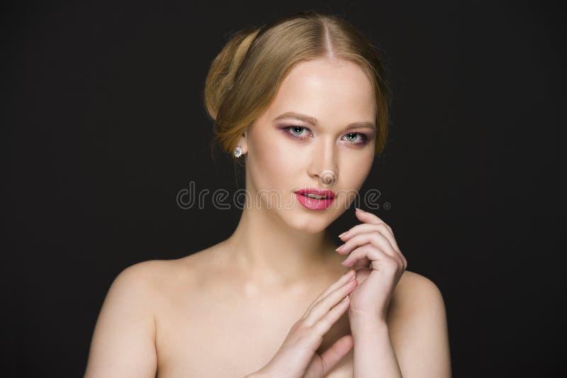 Junges Mädchen, das auf einem Schwarzen, nahtloser Hintergrund aufwirft stockfotos