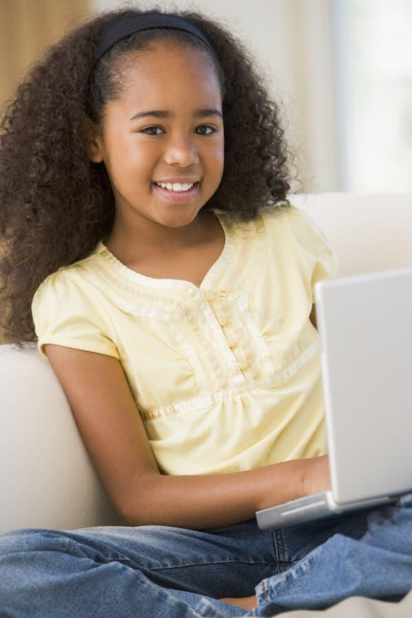Junges Mädchen, das auf einem Sofa, unter Verwendung eines Laptops sitzt lizenzfreies stockfoto