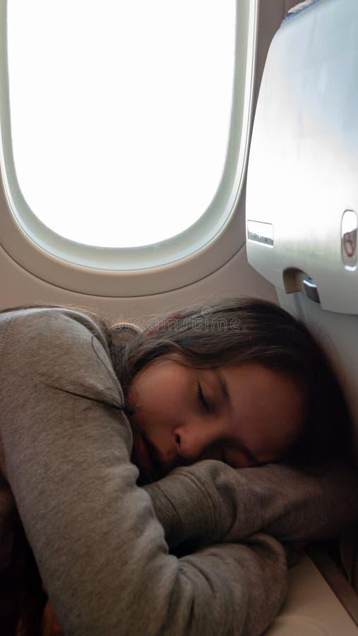 Junges Mädchen, das auf Flugzeug schläft stockbild