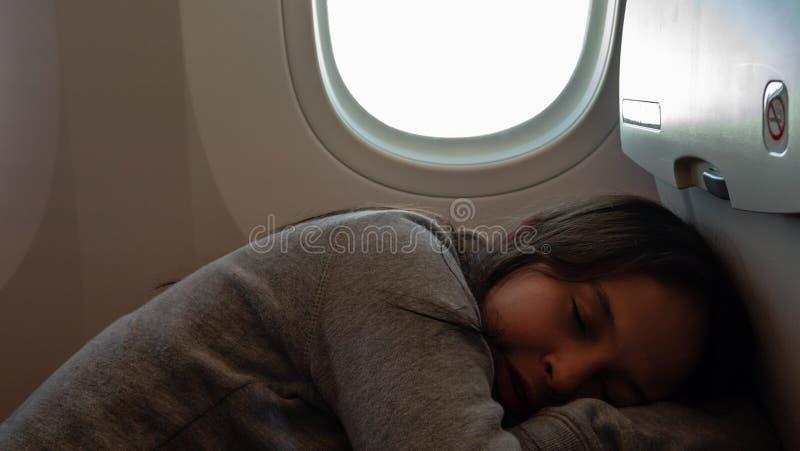 Junges Mädchen, das auf Flugzeug schläft stockfotografie