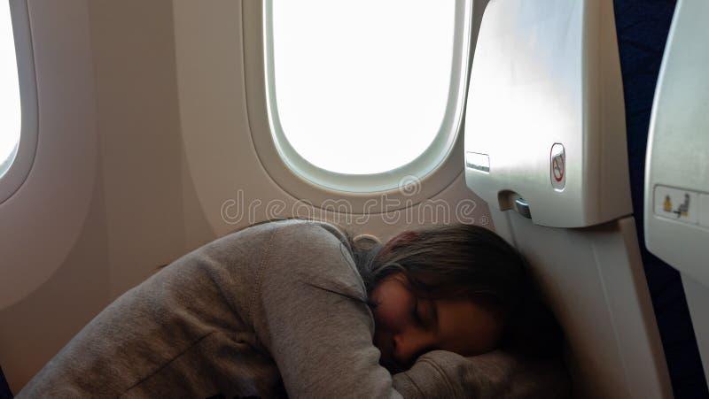 Junges Mädchen, das auf Flugzeug schläft lizenzfreie stockbilder