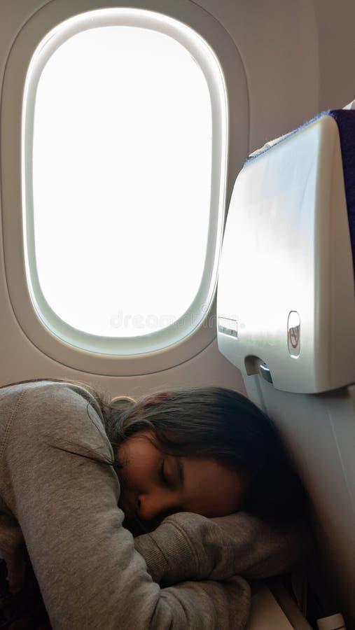 Junges Mädchen, das auf Flugzeug schläft lizenzfreie stockfotografie