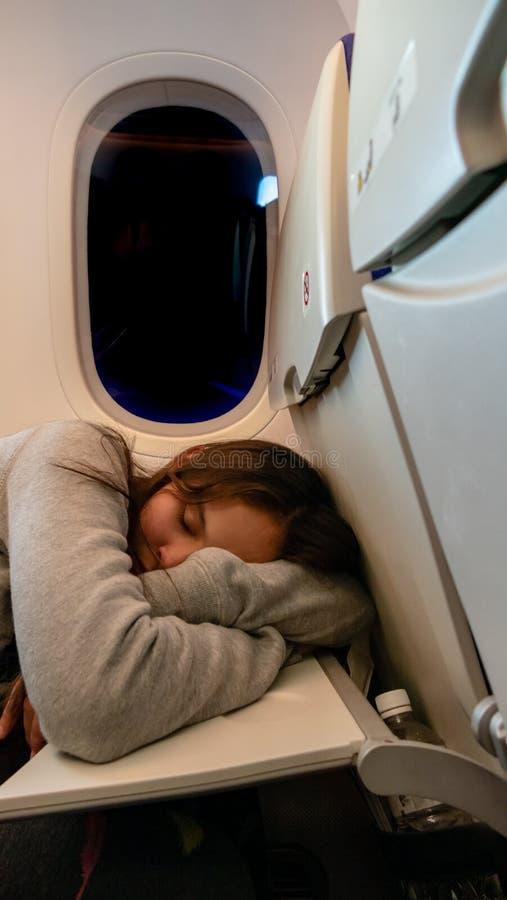 Junges Mädchen, das auf Flugzeug schläft lizenzfreies stockbild