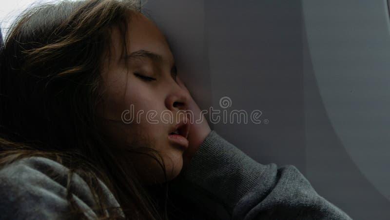 Junges Mädchen, das auf Flugzeug schläft stockfotos