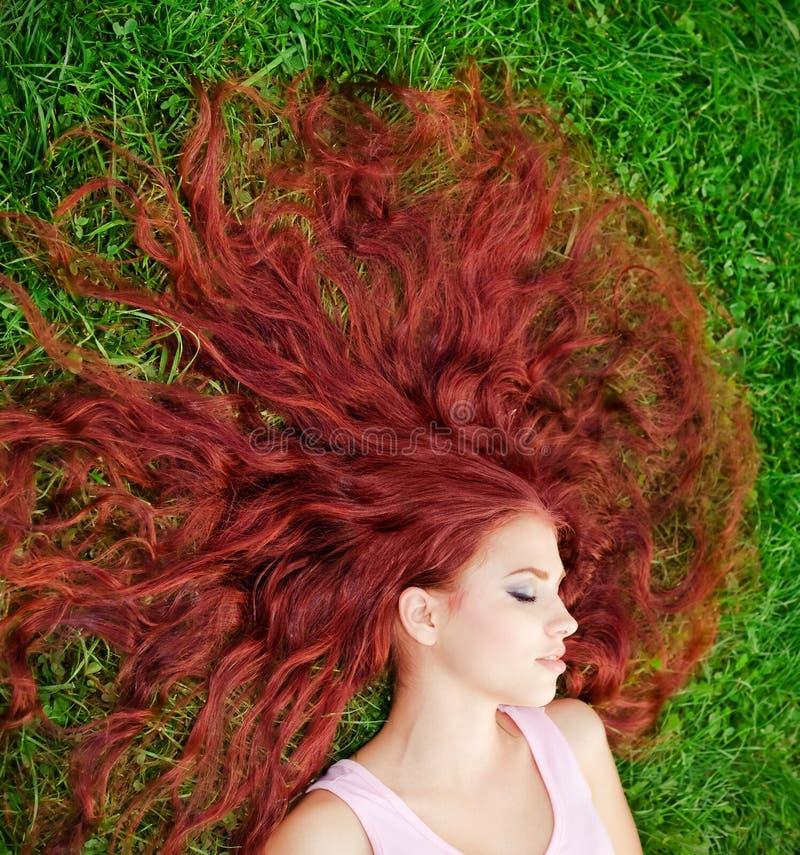 Junges Mädchen, das auf Gras liegt lizenzfreie stockbilder