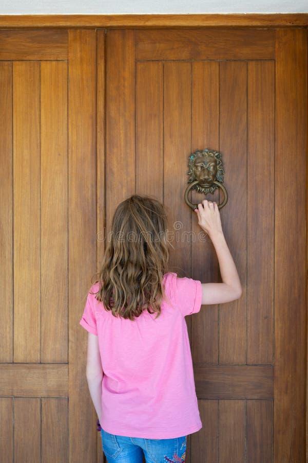 Junges Mädchen, das auf Haustür des Hauses klopft lizenzfreie stockfotos