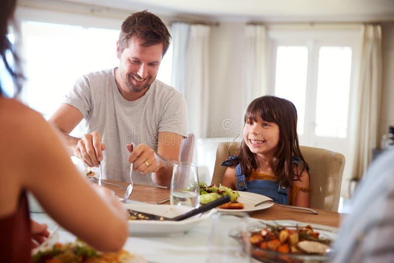 Junges Mädchen, das auf ihren Vati wartet, um Nahrung am Abendtische während einer Familienmahlzeit oben zu dienen, Abschluss lizenzfreie stockfotos