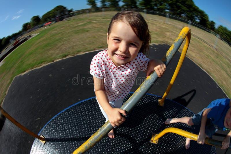 Junges Mädchen, das auf Karussell im sonnigen Park spielt lizenzfreies stockfoto
