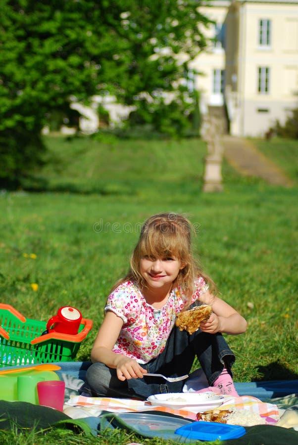 Junges Mädchen, das auf Picknick isst lizenzfreie stockfotos