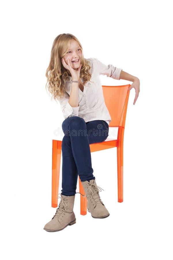 Junges Mädchen, das auf Stuhl sitzt stockfotos
