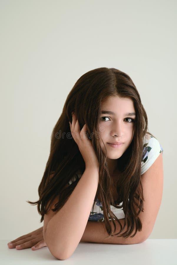 Junges Mädchen, das auf Tabelle sich lehnt lizenzfreie stockfotografie