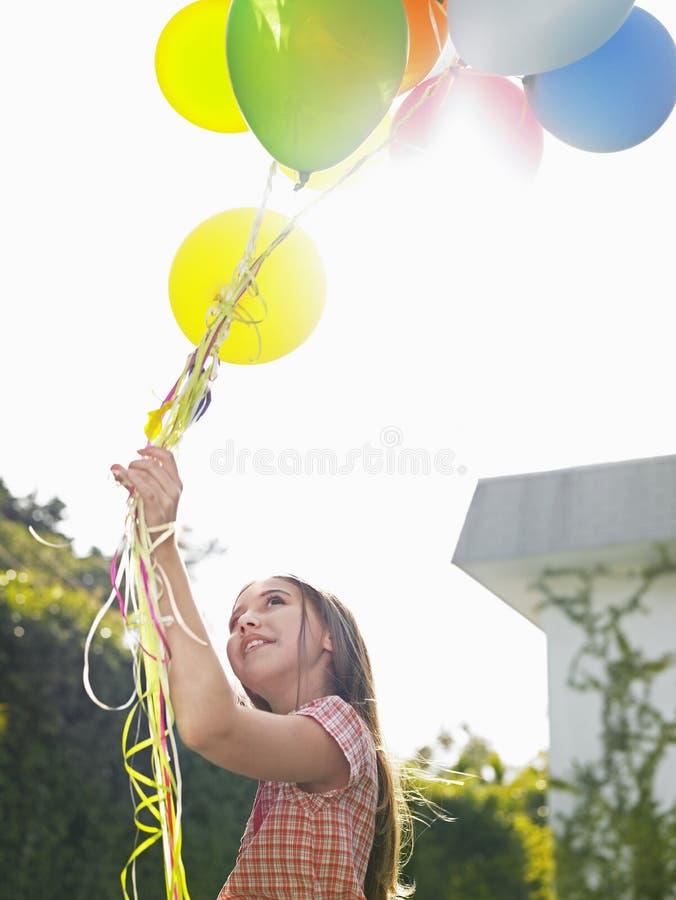 Junges Mädchen, das Ballone im Rasen hält stockfoto
