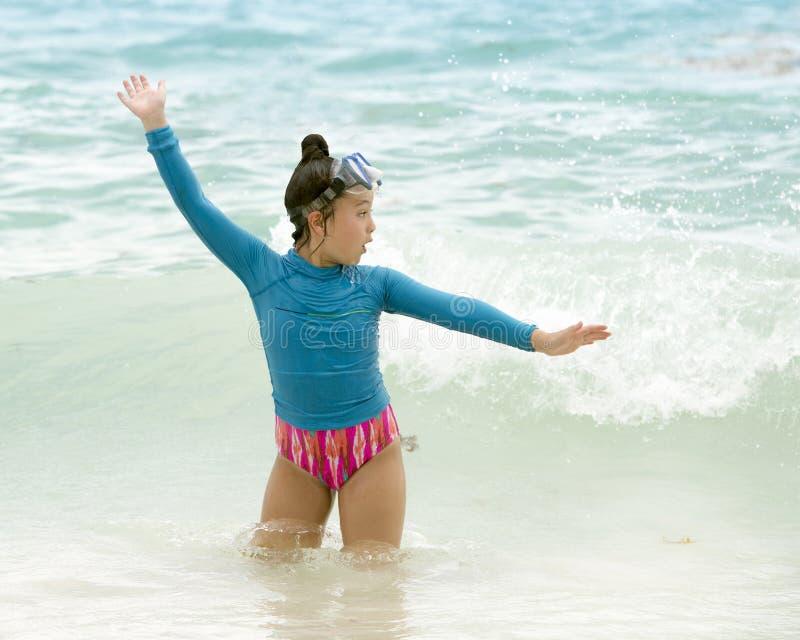Junges Mädchen, das in den Wellen der Karibischen Meere spielt stockfoto