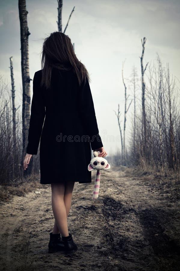 Junges Mädchen, das in der Hand auf die Straße mit Spielzeug geht stockfotografie
