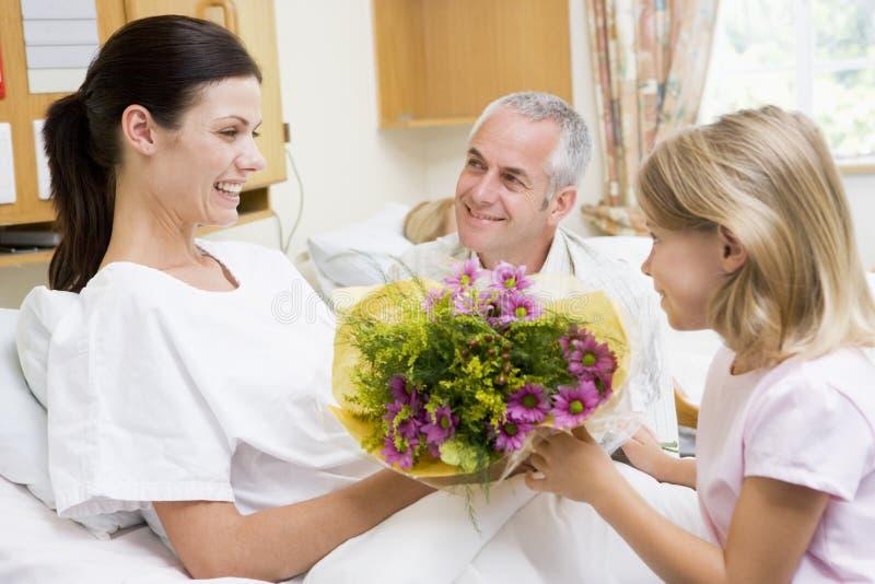 Junges Mädchen, das der Mutter im Krankenhaus Blumen gibt lizenzfreie stockbilder