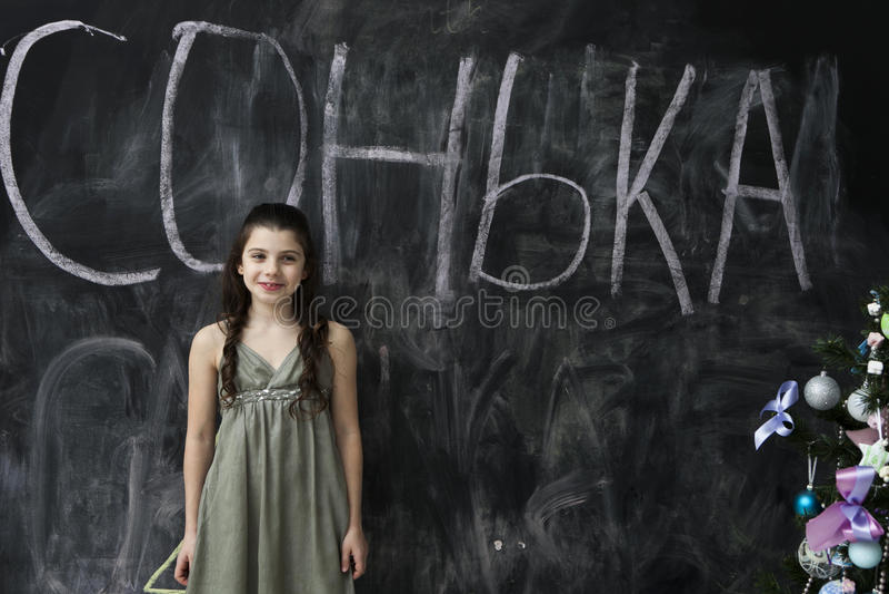 Junges Mädchen, das an der Tafel lächelt lizenzfreies stockfoto