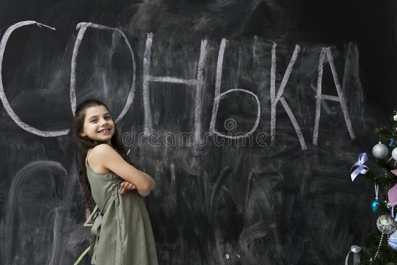 Junges Mädchen, das an der Tafel mit Kreide lächelt. lizenzfreies stockfoto