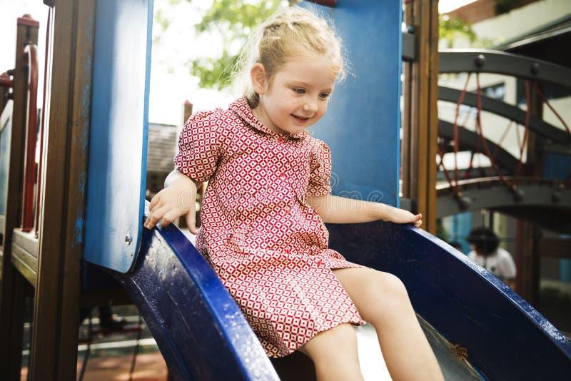 Junges Mädchen, das Dia im Spielplatz spielt stockfotos