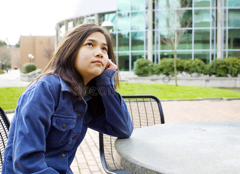 Junges Mädchen, das draußen denken sitzt lizenzfreies stockfoto