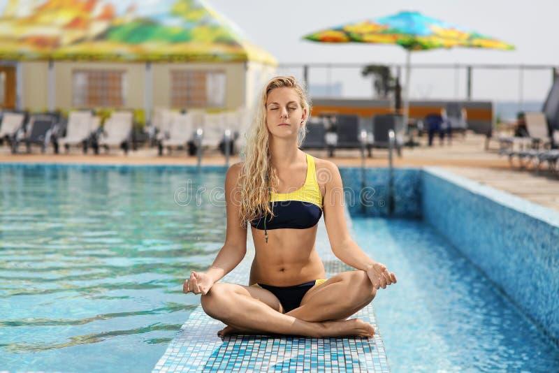 Junges Mädchen, das draußen durch das Pool sitzt und Übungen von tut lizenzfreies stockfoto
