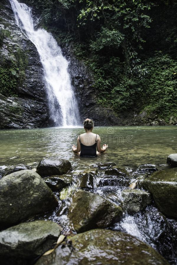 Junges Mädchen, das draußen im grünen Park auf Naturhintergrund meditiert lizenzfreie stockbilder