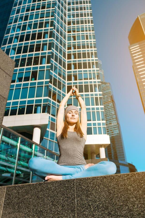 Junges Mädchen, das draußen Yoga in der Stadt tut lizenzfreie stockbilder