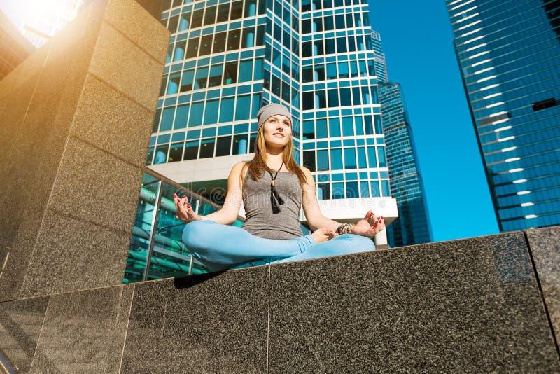 Junges Mädchen, das draußen Yoga in der Stadt tut stockbild