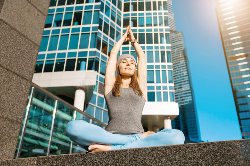 Junges Mädchen, das draußen Yoga in der Stadt tut lizenzfreies stockfoto