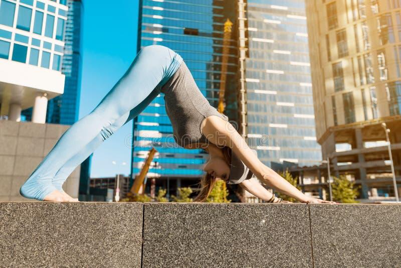 Junges Mädchen, das draußen Yoga in der Stadt tut stockfotografie