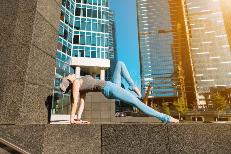 Junges Mädchen, das draußen Yoga in der Stadt tut stockbilder