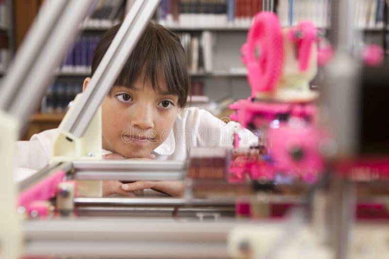 Junges Mädchen, das Drucker 3D aufpasst stockfotos