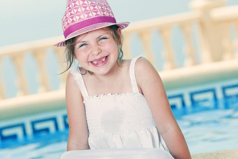 Junges Mädchen, das durch das Pool sitzt stockfotografie