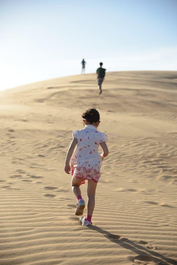 Junges Mädchen, das durch die Wüste folgt ihrer Familie geht lizenzfreie stockfotografie
