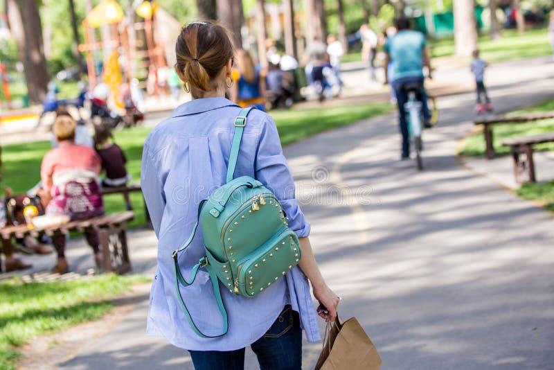 Junges Mädchen, das durch einen Stadtpark geht stockfoto