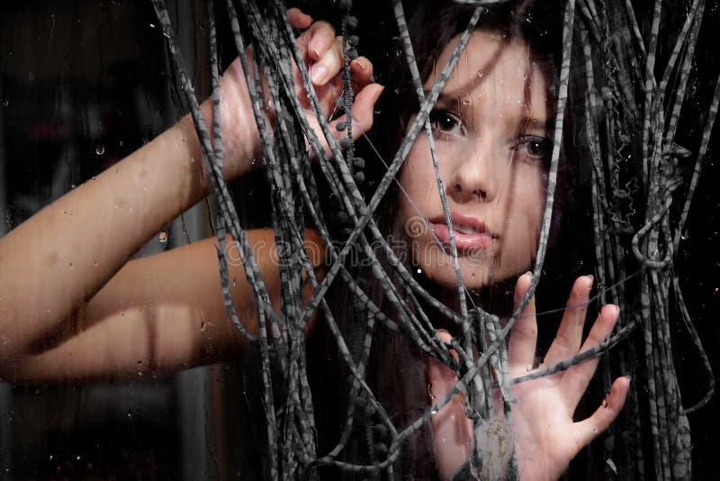 Junges Mädchen, das durch nasses Fenster schaut stockfoto